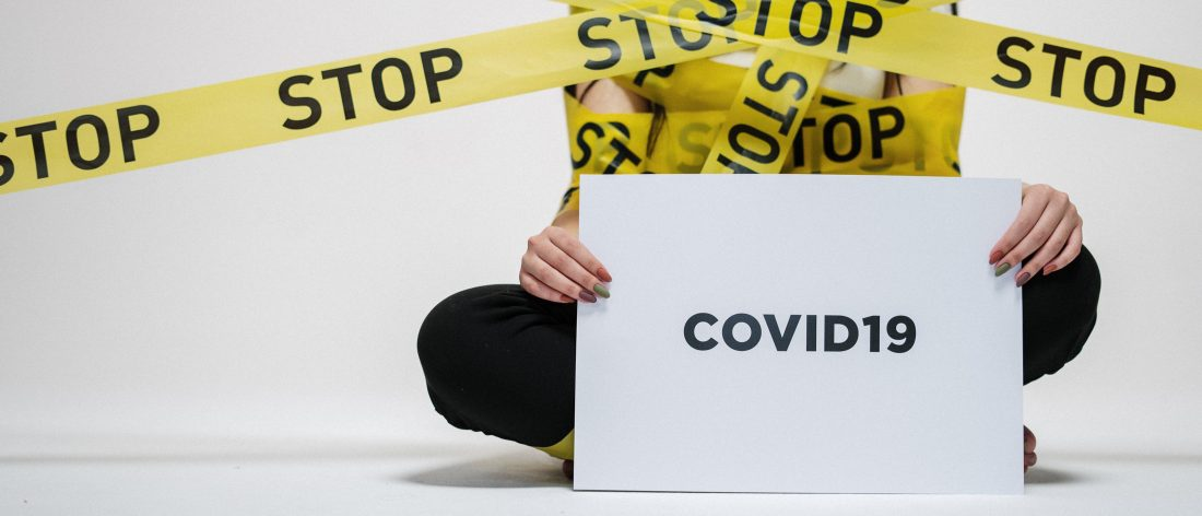 person wrapped in a sign that says stop holding another sign that reads COVID19