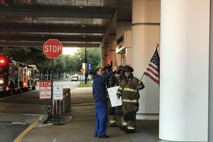 Man in scrubs takes selfie with firefighters