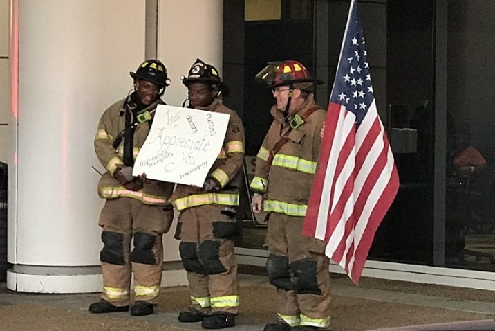 3 firemen in gear with American Flag