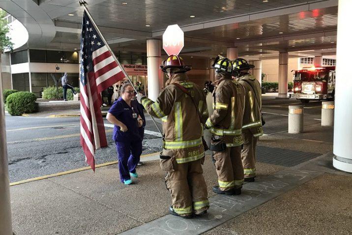 woman in scrubs talks to firefighters