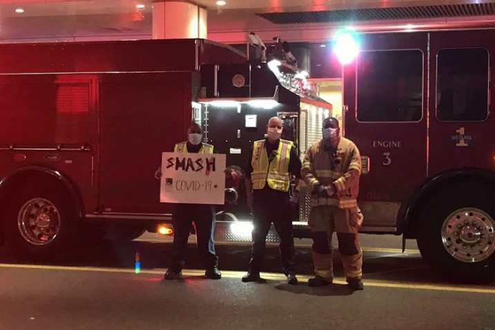 three firefighters stand beside truck holding sign
