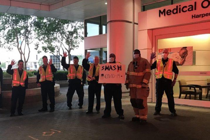 six firemen stand outside hospital