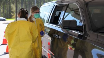 two nurses giving test near a car