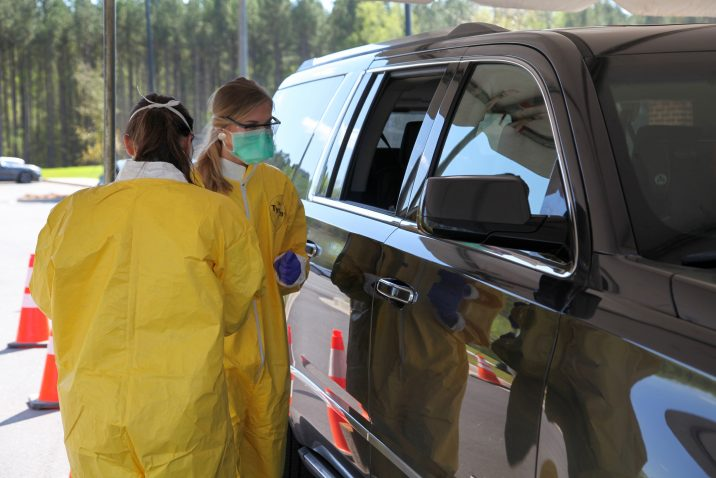 two nurses giving test near a car