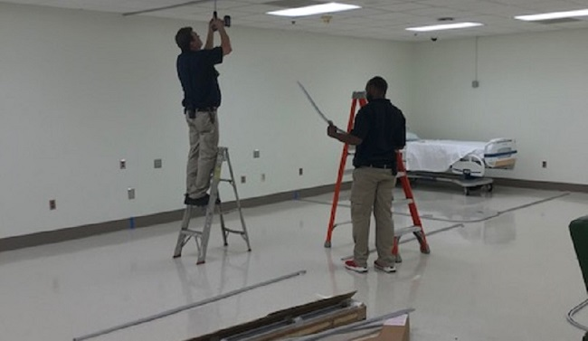 Two employees, one on ladder with drill, the other holds wire