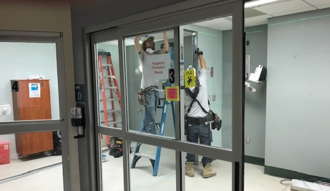 two men work inside glass doors of hospital room
