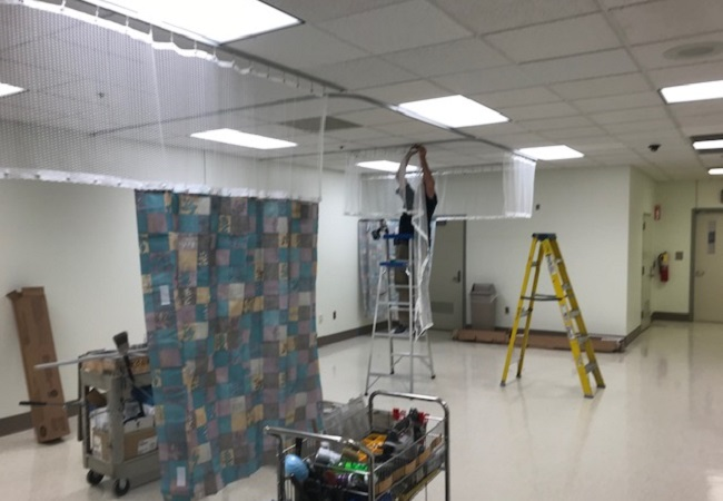 Man on ladder installing curtain in ceiling
