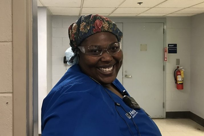 Woman in blue scrubs smiles