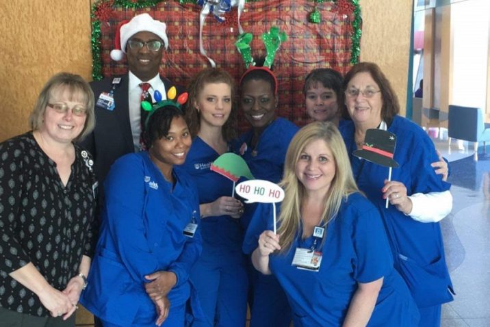 A group of women in blue scrubs pose for a 2019 Christmas photo.