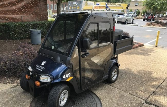 Navy blue Cushman golf cart with Augusta University logo on front