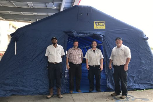 Four men stand at large blue tent