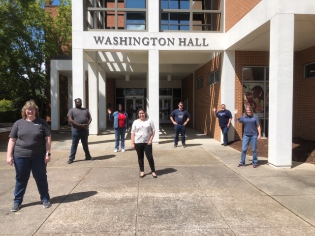 7 people stand outside Washington Hall