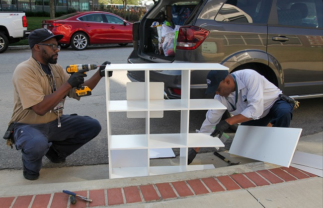 two men take apart shelving unit
