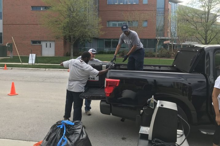 three men load a TV into black truck