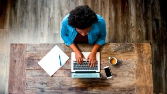 woman works on wood desk at home