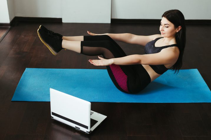 Woman exercising looking at computer