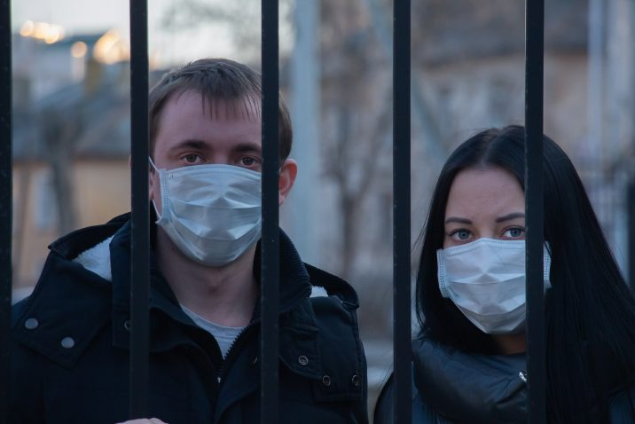 A man and woman with masks behind bars