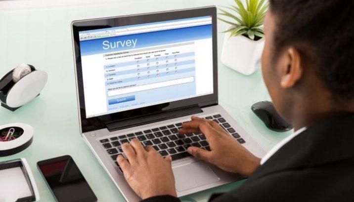 man taking survey on laptop computer