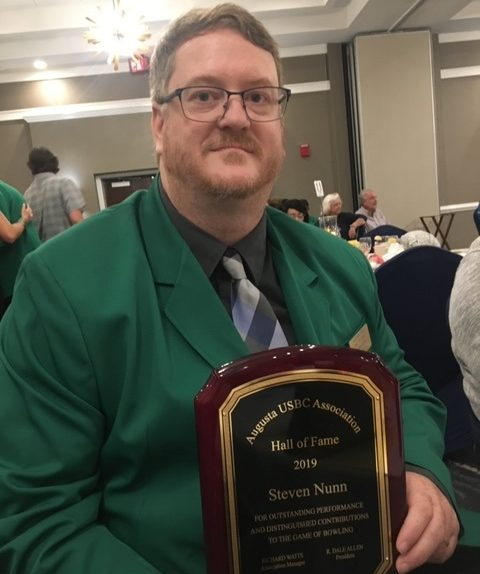 man in green sport coat with award