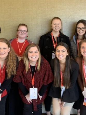 11 students posing for a photo at a conference