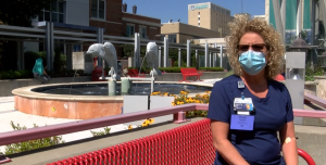 Nurse on red bench wearing mask and blue scrubs