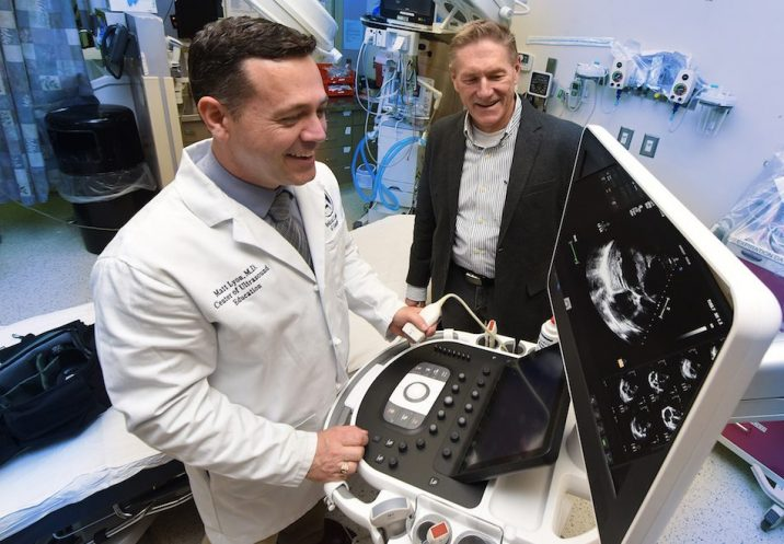 Two men looking at a portable ultrasound machine