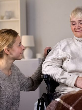 Young woman kneeling next to older woman in wheelchair