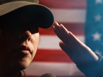 Woman saluting in front of flag