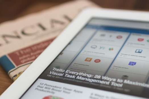 An image of a newspaper and tablet.