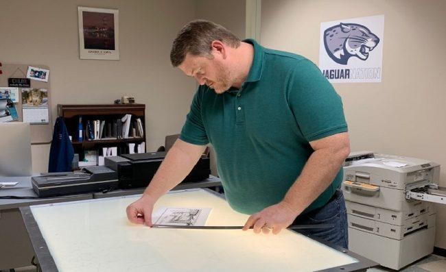 man in green shirt looks over file