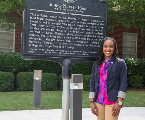 woman stands in front of history Stoney Nurses Home sign