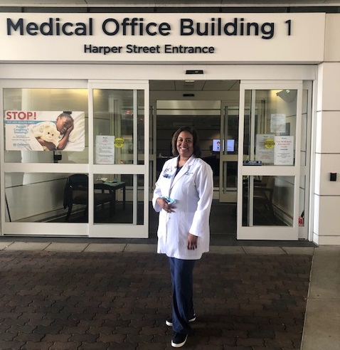 woman in white coat in front of medical building