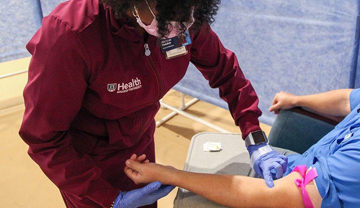 A nurse preparing to draw blood.