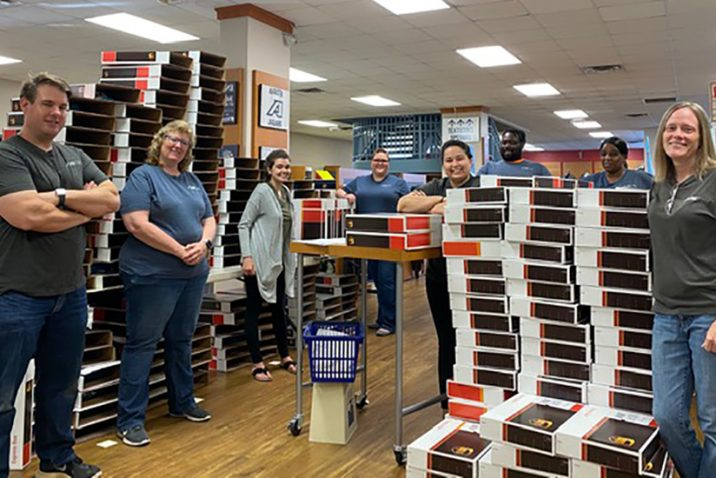 employees stand in bookstore among boxes