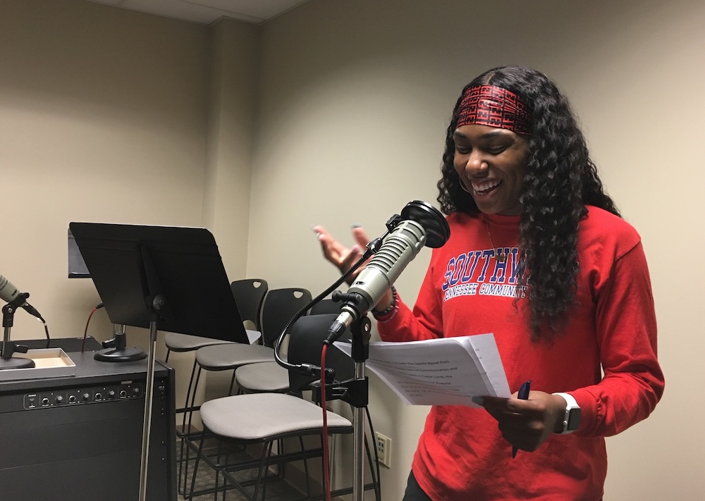 Woman speaking into a microphone.
