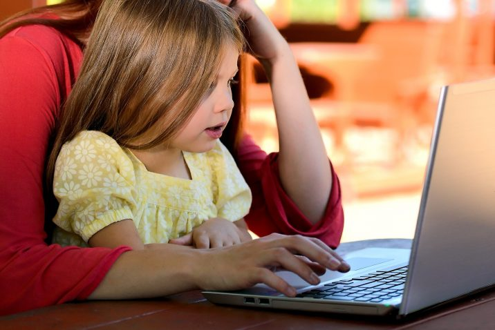 A little girl sitting on her mother's lap while looking at a computer.