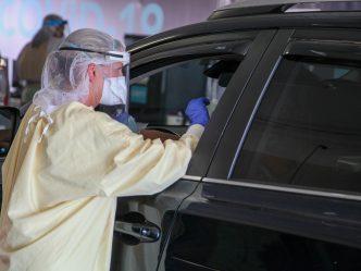 nurse performs test by car