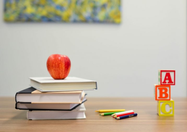 A photo of an apple on top of books next to letters.