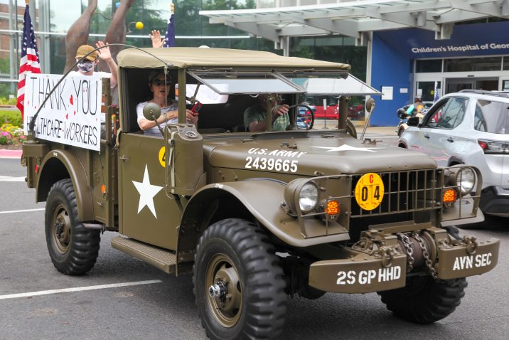 military truck with people inside waving