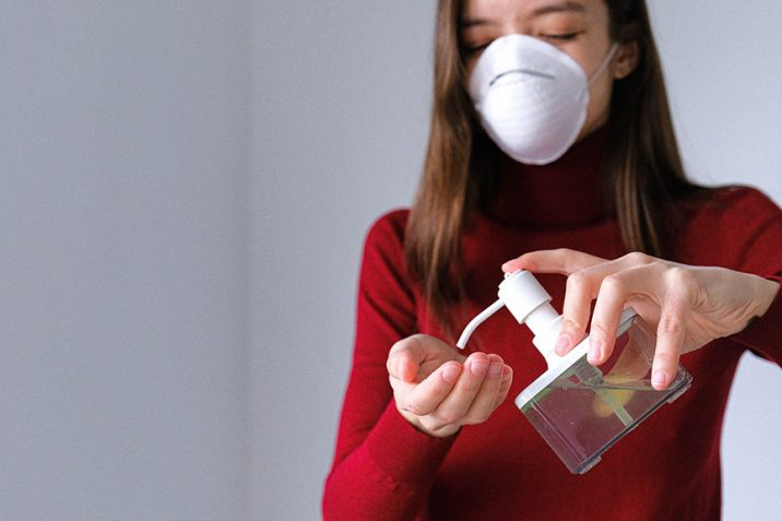 Woman in mask using hand sanitizer