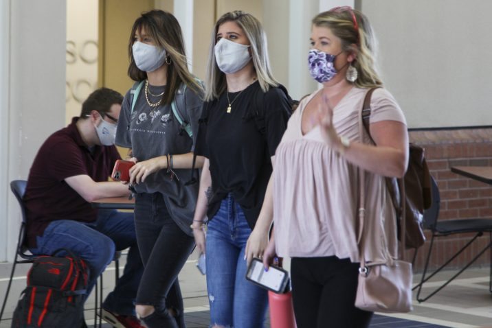 Three female college students walking wearing face masks.
