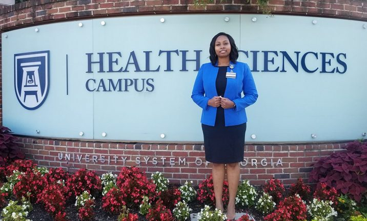 Woman stands in front of Health Sciences Campus sign