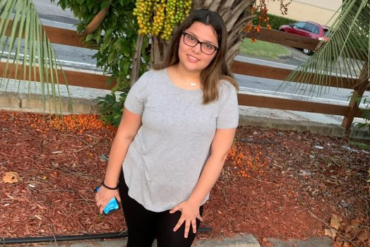 Teenage girl in a grey shirt and black pants.