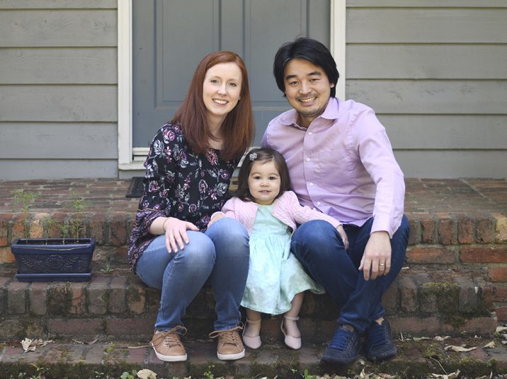 Wife, daughter and husband sit on steps