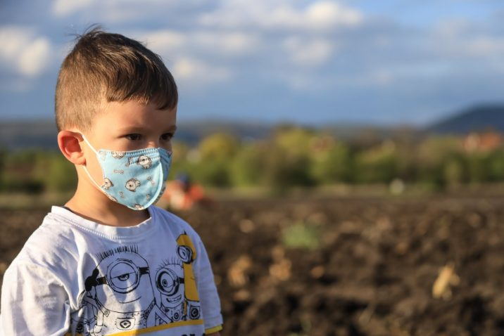 Small boy wearing a face mask while standing outside.