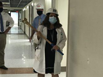 female physician holds sledgehammer