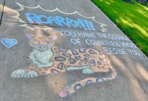 "chalk art of a Jaguar, with text surrounding it: ""Roarrr!!! You have the courage of countless voices beside you."""