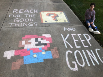 "Student sits beside driveway chalk art. Art is a drawing of Mario, captioned ""Reach for the good things and keep going."""