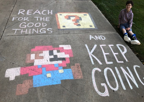"""Student sits beside driveway chalk art. Art is a drawing of Mario, captioned """"Reach for the good things and keep going."""""""