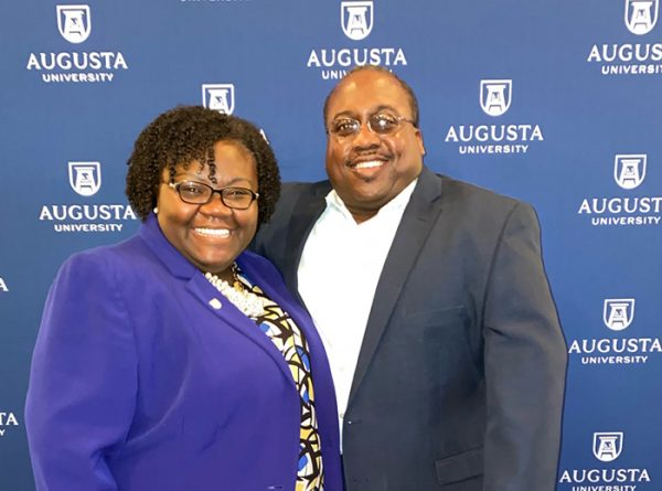 woman and man in front of Augusta University background